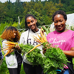 Students on a farm smiling and holding carrots